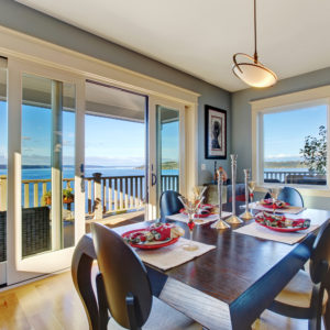 Light blue dining area with sliding glass door to walkout deck. Served wooden table with chairs; Shutterstock ID 222732964; PO: P C Henderson; Job: For use on website, brochure